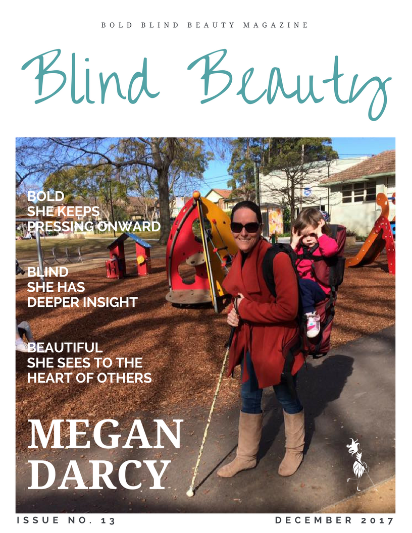 Meg is looking fabulous in oversized shades as she poses for the camera with white cane in hand and her daughter, Emily in her carrier on Meg's back. Meg is wearing a stylish red coat, blue jeans, and knee-high tan boots. They are in a playground on a bright, sunny day.