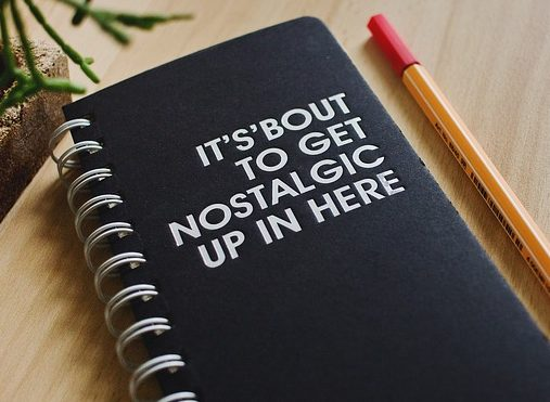 "White text ""Its Bout To Get Nostalgic Up In Here"" in on a black spiral bound journal with a pencil laying next to it."