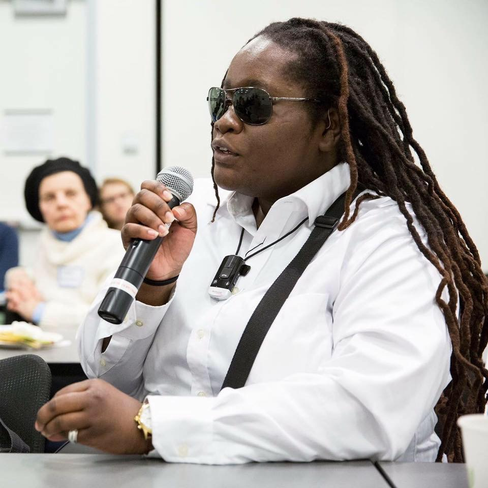 Casandra Xavier sits at a table with a microphone at Perkins School for the Blind, was in the middle of asking a question. She wears polarized aviators. In the background are two people glancing attentively at her while she asks her question. In this photo, her dreadlocks are draped down her back with a heavy, natural brownish-red color. Around her neck is a phone loop for her hearing aids, she wears a crisp white button down shirt with her braille display strap exposed. She was fully aware of Perkins photographer.